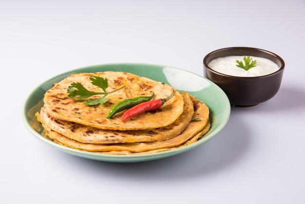 전통적인 인도 음식 aloo paratha 또는 감자 박제 납작한 빵. 다채로운 또는 나무 배경 위에 토마토 케첩과 커드와 함께 제공됩니다. 선택적 초점