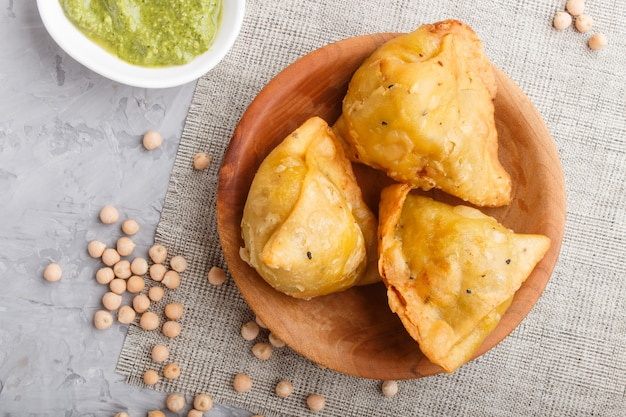 Traditional indian food samosa in wooden plate with mint chutney. top view.