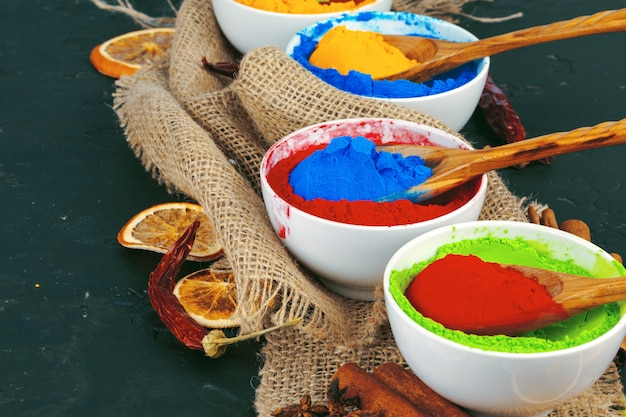 Traditional indian holi colours powder, spices on dark rustic background