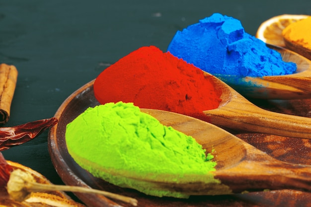 Traditional indian holi colours powder, spices on dark rustic