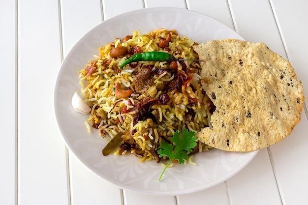 Бирьяни из традиционной индийской баранины, подается с раитой и хрустящим паппадамом на белой поверхности выборочный фокус аутентичная кухня