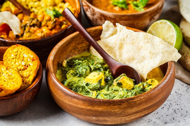 Traditional indian palak paneer in wooden bowl on white table.