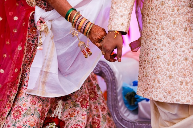 Traditional indian wedding ceremony, groom holding bride hand