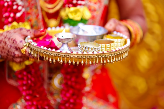 Traditional indian wedding ceremony in hinduism  holding puja thali and oil lamp in hand