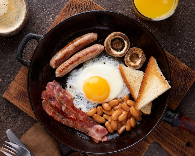 Traditional irish brunch with ham grilled sausages toast mushrooms beans and fried eggs