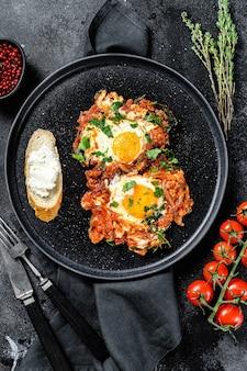 Традиционные блюда израильской кухни шакшука. жареное яйцо с помидорами и паприкой. черный фон. вид сверху.