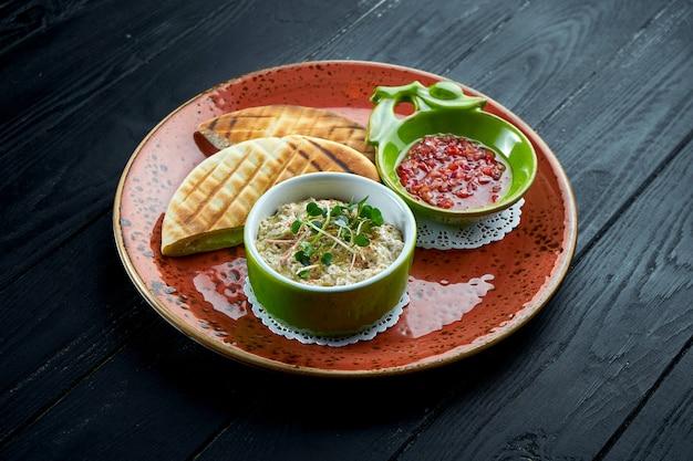 Традиционный израильский или восточный баба гануш с овощной сальсой и лавашем, подается в красной тарелке на темном фоне.
