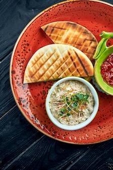 야채 살사와 피타를 곁들인 전통적인 이스라엘 또는 동양의 바바 가누 쉬는 어두운 표면에 빨간 접시에 담겨 제공됩니다. 가지 레스토랑 요리