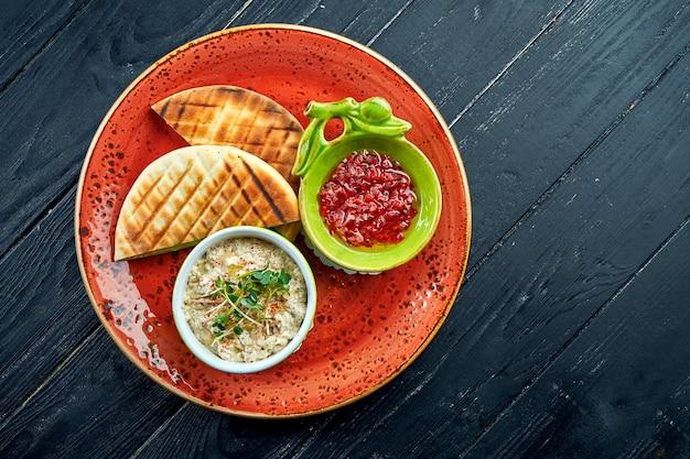伝統的なイスラエルまたはオリエンタルのババガヌーシュと野菜のサルサとピタを木製のテーブルの赤いプレートでお召し上がりいただけます