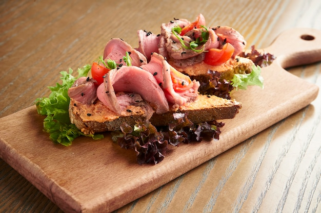 Traditional italian antipasti - bruschetta with roast beef and tomato on a wooden board on a wooden surface. film effect during post. soft focus