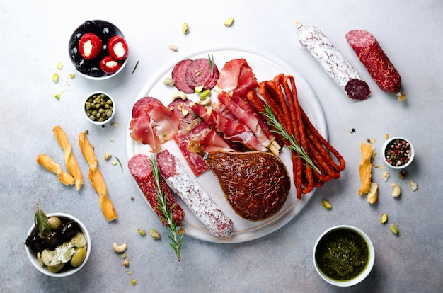 Traditional italian antipasto, cutting board with salami, cold smoked meat, prosciutto, ham, cheese, olives, capers on grey.