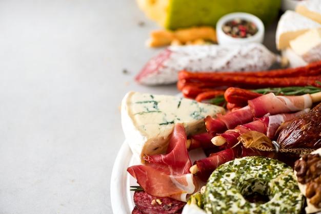 Traditional italian antipasto, cutting board with salami, prosciutto, ham, pork chops, olives