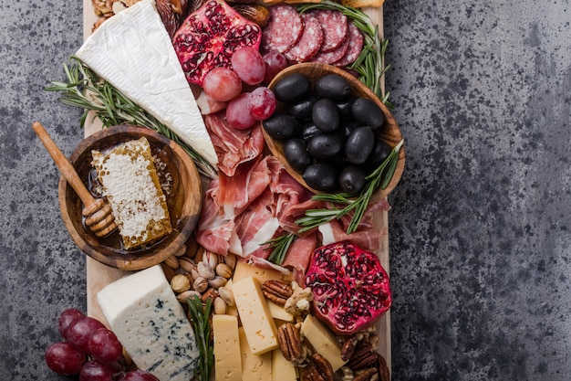 Traditional italian antipasto plate. assorted cheeses on wooden cutting board. brie cheese, cheddar slices, gogonzola, walnuts grapes, olives, prosciutto, rosemary and glass of red wine. top view