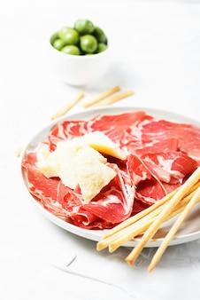 Традиционная итальянская закуска с сыром, ветчиной и хлебными палочками, селективный фокус