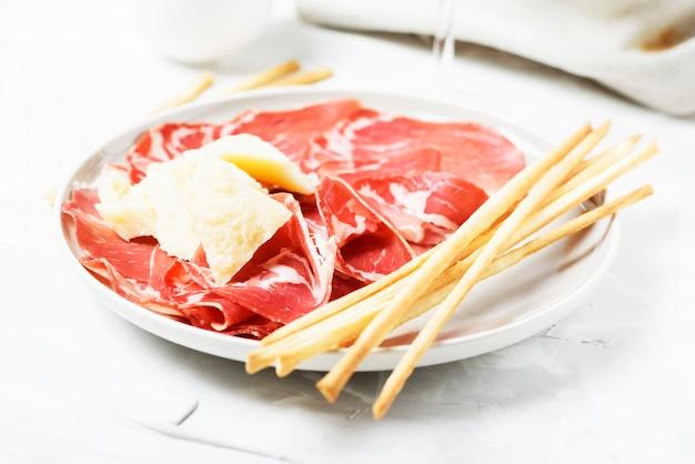 Традиционная итальянская закуска с сыром, ветчиной и хлебными палочками, выборочный фокус