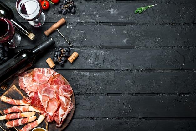 黒の素朴なテーブルに赤ワインを添えた伝統的なイタリアの前菜。