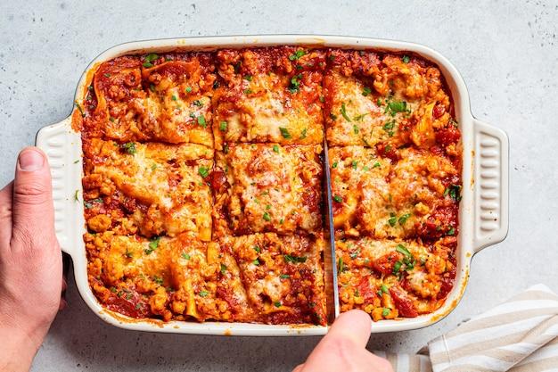 접시에 고기와 치즈를 곁들인 전통적인 이탈리아 구운 라자냐. 이탈리아 요리 개념.