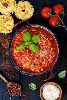 古い暗い木製の背景に鍋に伝統的なイタリアのボロネーゼ ソース。トップ ビュー、コピー スペース