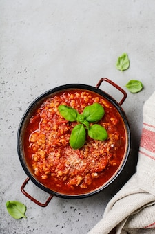 Traditional italian bolognese sauce in saucepot an old dark wooden background