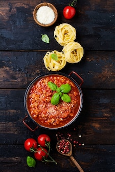 Traditional italian bolognese sauce in saucepot an old dark wooden surface. top view, copy space
