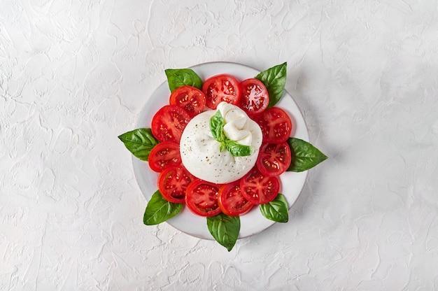 바질과 토마토를 곁들인 버팔로 또는 소의 크림과 우유로 만든 전통 이탈리아 부라타 치즈