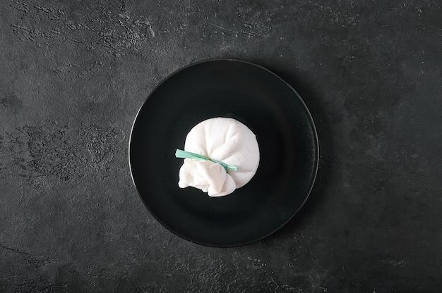 흑연 배경 상단 뷰 복사 공간에 있는 어두운 접시에 있는 전통적인 이탈리아 부라타 치즈