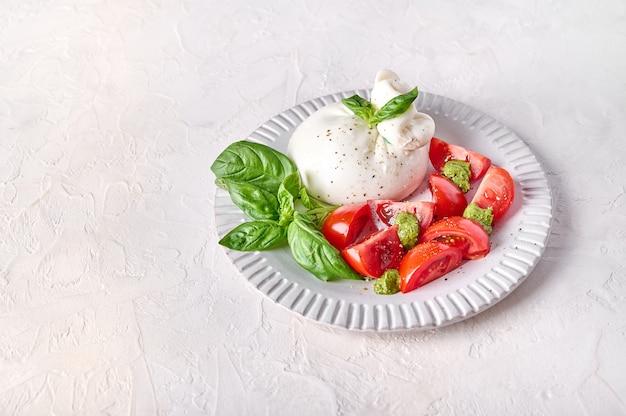 Традиционный итальянский сыр буррата с базиликом и помидорами на светлом фоне крупным планом