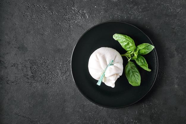 Традиционный итальянский сыр буррата с базиликом на темной тарелке с копией пространства