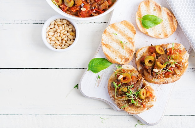 Традиционная итальянская капоната и тосты на деревянном белом столе. сицилийская капоната Premium Фотографии
