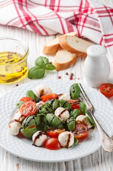 Traditional italian caprese salad with mozzarella, cherry tomatoes,