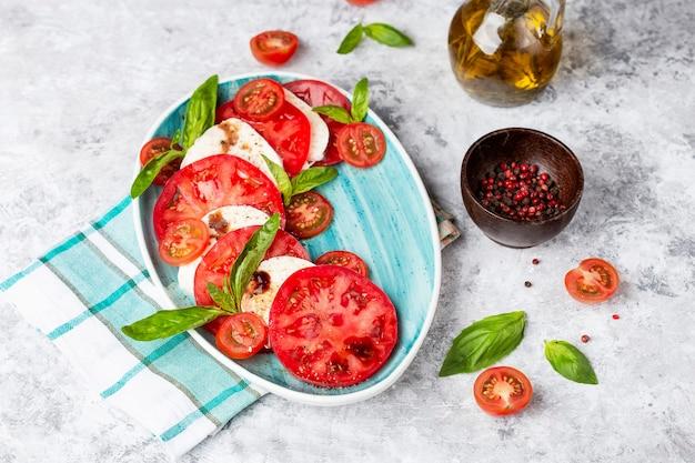 スライストマト、モッツァレラチーズ、バジル、オリーブオイルを使った伝統的なイタリアのカプレーゼサラダ