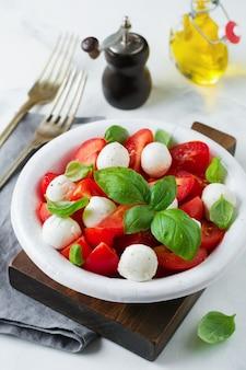 白い古いセラミックプレートの明るい大理石の背景にトマト、マオザレラチーズ、バジルの伝統的なイタリアのカプレーゼサラダ。