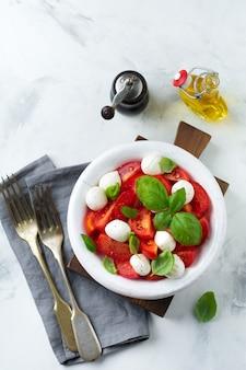白い古いセラミックプレートの明るい大理石の表面にトマト、マオザレラチーズ、バジルを添えた伝統的なイタリアのカプレーゼサラダ。セレクティブフォーカス。上面図。