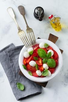Традиционный итальянский салат капрезе с помидорами, сыром маоцарелла и базиликом на светлой мраморной поверхности на старой белой керамической тарелке