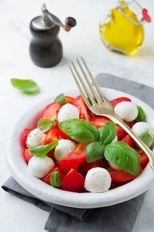 白い古いセラミックプレートの明るい大理石の表面にトマト、マオザレラチーズ、バジルを添えた伝統的なイタリアのカプレーゼサラダ