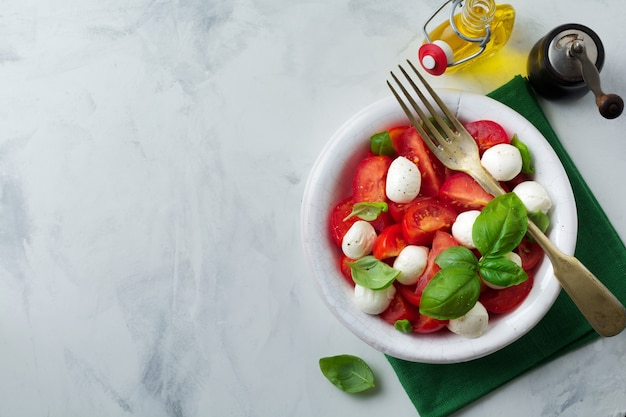 Traditional italian caprese salad with tomatoes, maozzarella cheese and basil on a light marble background in a white old ceramic plate.