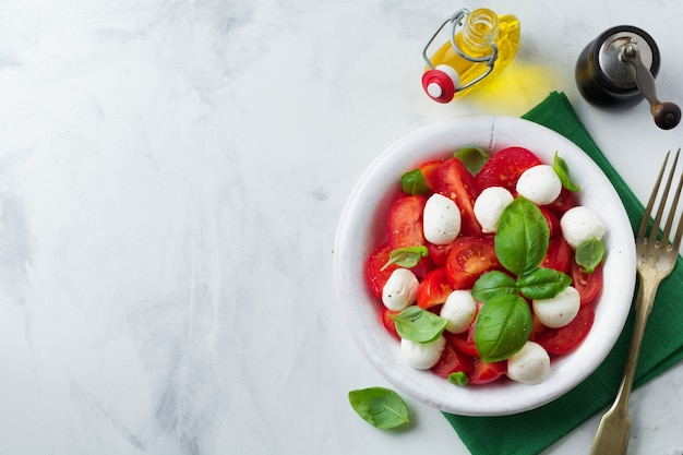 Traditional italian caprese salad with tomatoes, maozzarella cheese and basil on a light marble surface in a white old ceramic plate