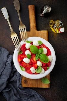 白い古いセラミックプレートの暗い背景にトマト、モッツァレラチーズ、バジルの伝統的なイタリアのカプレーゼサラダ。
