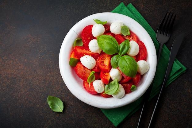 Традиционный итальянский салат капрезе с помидорами, сыром моцарелла и базиликом на темной поверхности в старой белой керамической тарелке