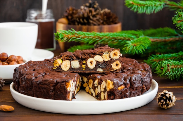 Traditional italian christmas dessert with nuts and dried fruit on a white plate on a dark wooden background.