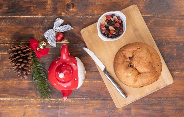 Традиционный итальянский рождественский фруктовый торт панеттоне и чай на деревянной доске