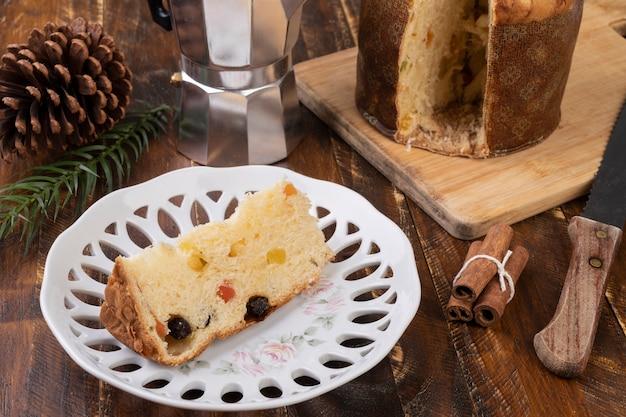 Традиционный итальянский рождественский фруктовый торт с ломтиком на тарелке