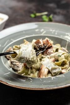 伝統的なイタリア料理、ポルチーニ茸と鶏肉のクリーミーソースのタギアテルパスタ。料理のコンセプト、縦の画像。コピースペース。