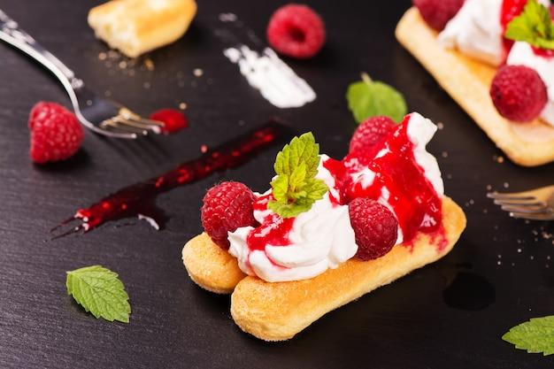 Traditional italian dessert - tiramisu cake with raspberry and mint on black stone background.