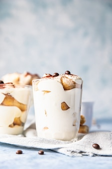 Traditional italian dessert tiramisu in glass, light stone surface
