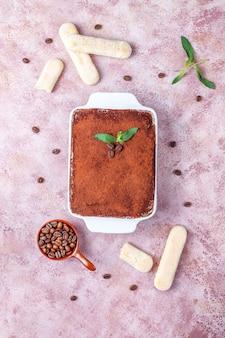 Традиционный итальянский десерт тирамису в керамической пластине, вид сверху.