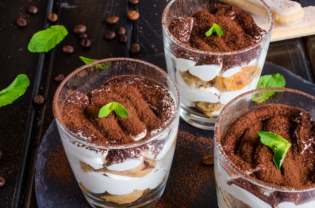 Traditional italian dessert tiramisu served in a glass on a dark surface