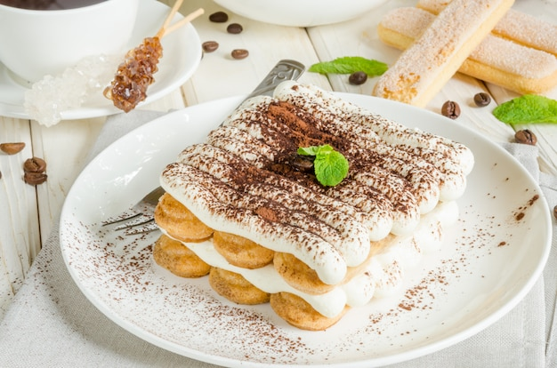 Traditional italian dessert tiramisu served on a plate with a cup of coffee on a white wooden surface