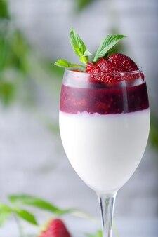 Traditional italian dessert vanilla strawberry panna cotta in verina with fresh berries copy space