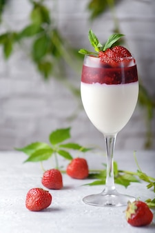 Traditional italian dessert vanilla strawberry panna cotta in verina with fresh berries. copy space.